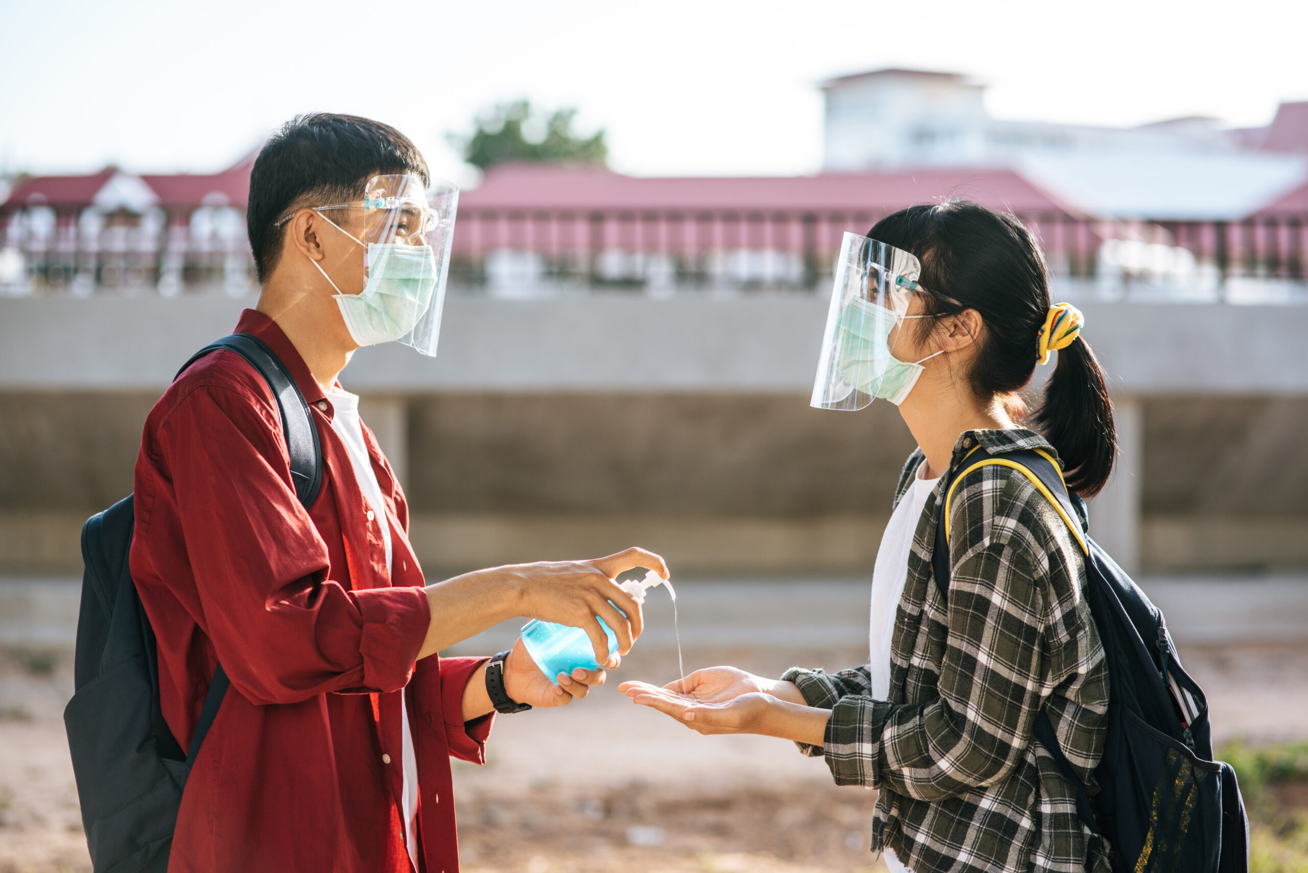 Male and female students wear masks and squeeze the gel to wash
